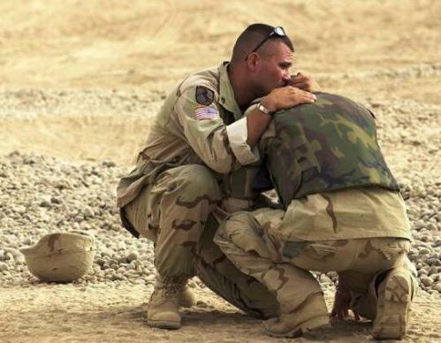 A Marine consoling his fellow Marine