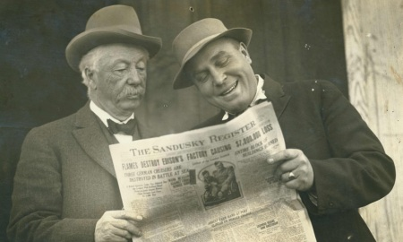 Two men reading a newspaper in 1914