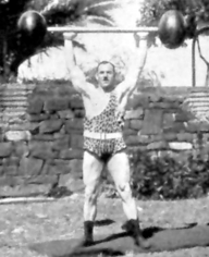 Old school strong man Herman Goerner demonstrating the overhead press.  Good exercise form, terrible fashion choice.