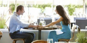 Couple Holding Hands At Outdoor Restaurant Table