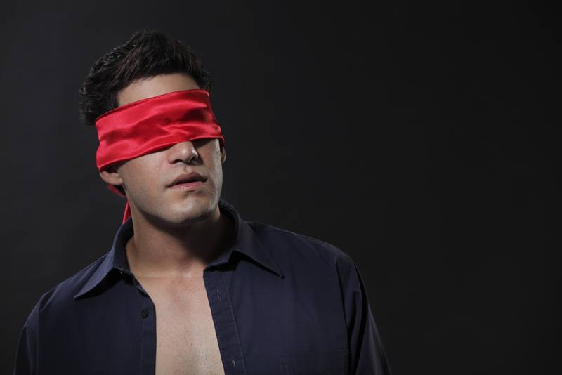 Man-blindfolded-with-red-cloth