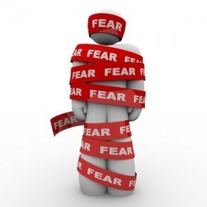 A man is wrapped in red tape reading fear representing the paralysis of being afraid and unable to move or act in the face of danger or something that scares or