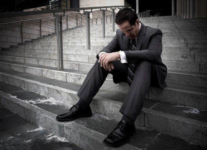 A distraught man sits on the steps of an office building.