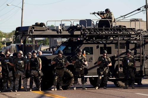 Law enforcement officers, including a sniper perched atop an armored vehicle, watch as demonstrators protest the fatal shooting of Michael Brown, in Ferguson, Mo., Aug. 13, 2014. The police chief of this St. Louis suburb said Wednesday that Brown injured the officer who later fatally shot the unarmed 18 year old ? though witnesses dispute that such an altercation occurred. (Whitney Curtis/The New York Times)