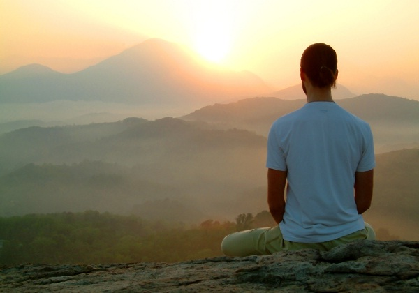 man-meditating-on-mountain