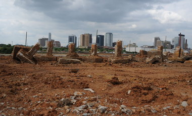 Site ready for construction, with city skyline in background