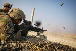 A U.S. soldier from the 3rd Cavalry Regiment is watched as he fires a squad automatic weapon during a training mission near forward operating base Gamberi, in the Laghman province of Afghanistan December 15, 2014. REUTERS/Lucas Jackson (AFGHANISTAN - Tags: CIVIL UNREST MILITARY)