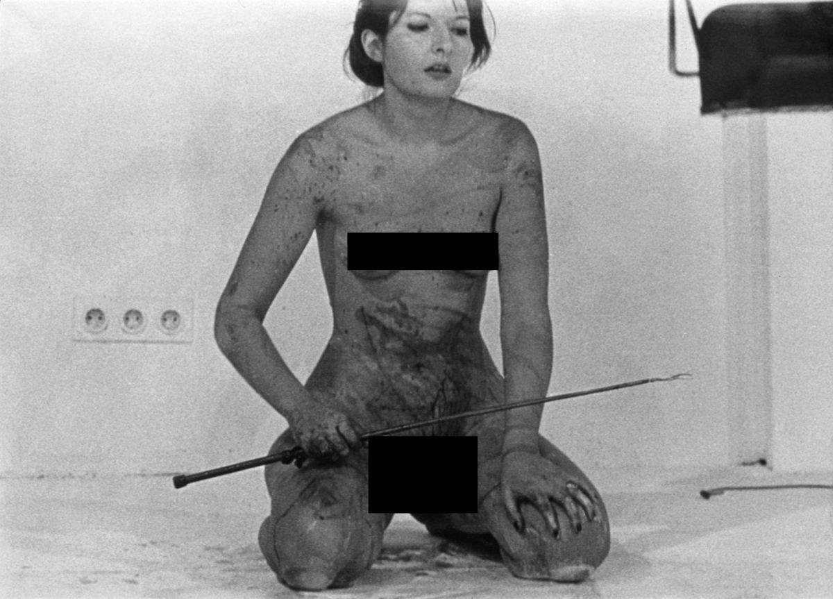 Abramovic carving a pentagram in her flesh with a blade to show her artistic side