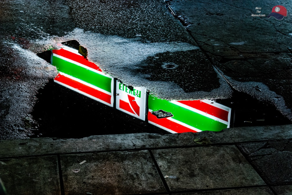 7-Eleven Sign Reflected in a Puddle