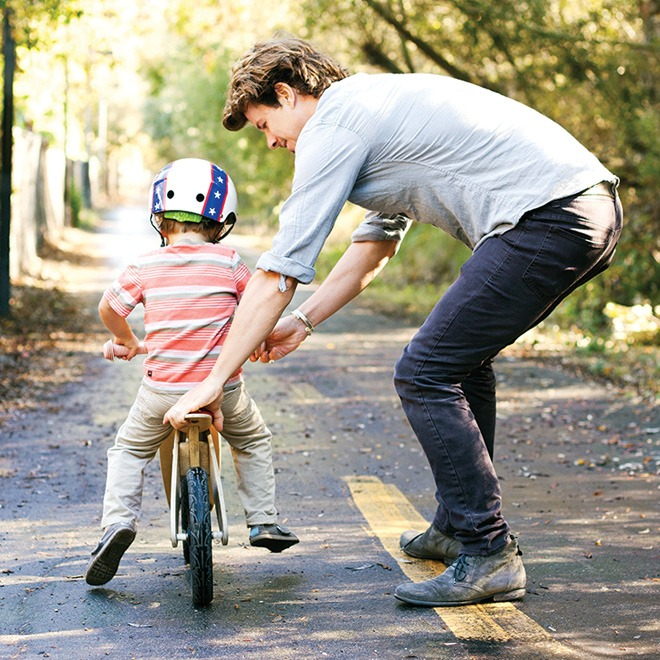 father teaching son to ride bike